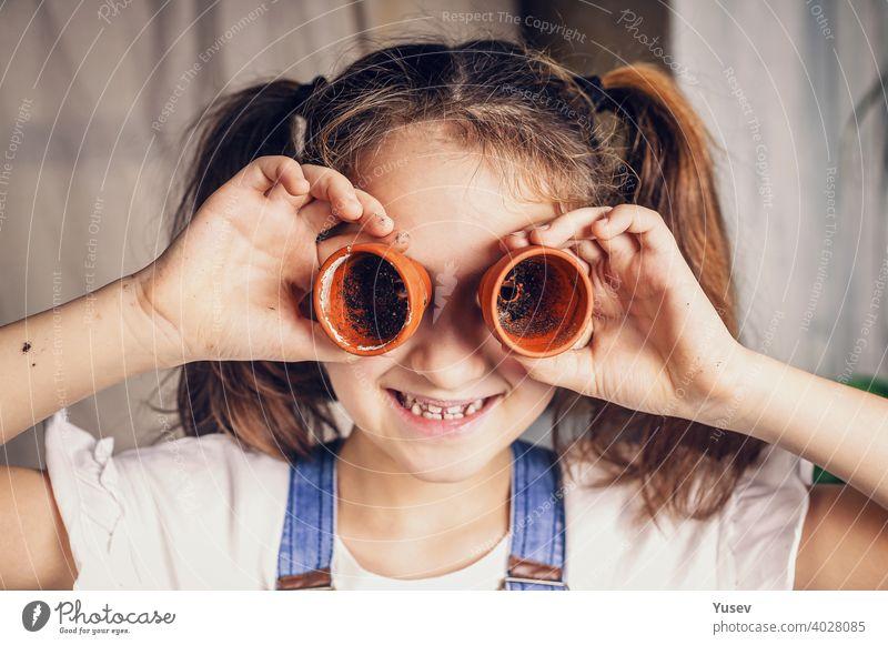 nettes kleines Mädchen hat Spaß daran, Blumentöpfe als Brillen zu benutzen. Kinderbelustigungen, glückliche Kindheitsmomente. kaukasische Ethnie. Nahaufnahme