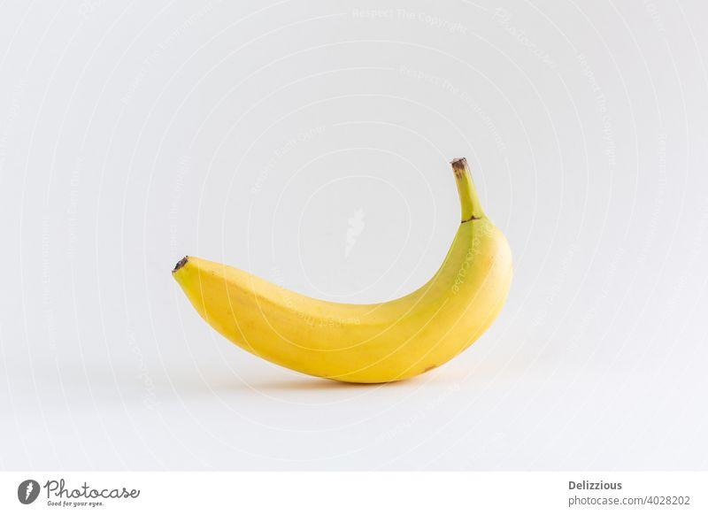 Eine einzelne Banane auf weißem Hintergrund, mit Kopierraum abstrakt appetitlich bananengelb Kalzium Konzept Textfreiraum Dessert Diät essen Essen Energie
