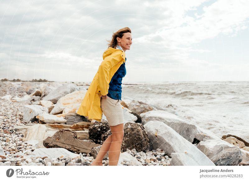 Frau mit wehenden Haaren in einem gelben Regenmantel schaut auf das Meer Meeresufer Wind gelber haare im wind glücklich Sommer Natur Freiheit