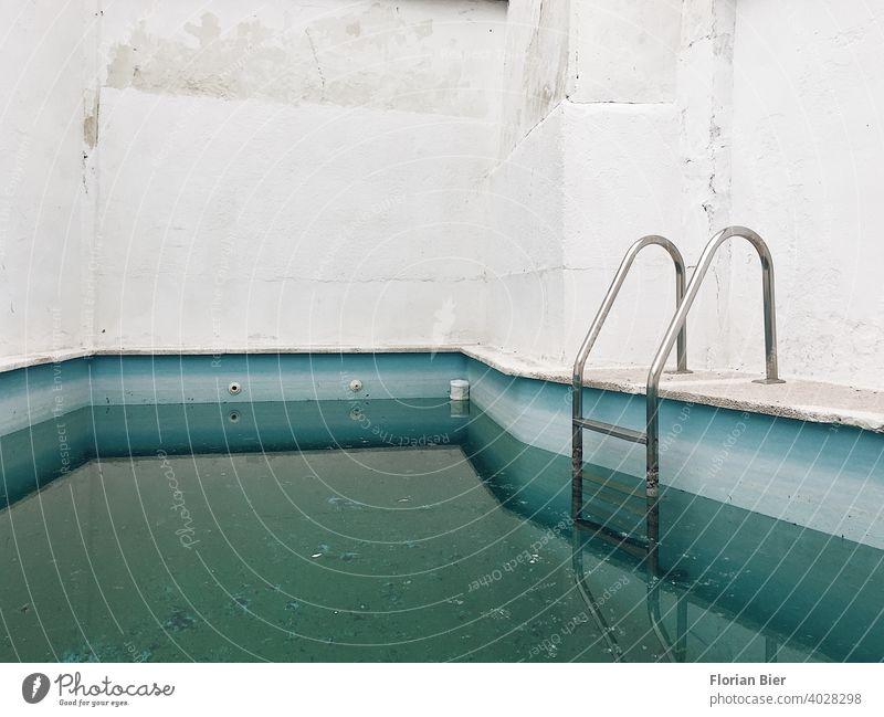 Befülltes gemauertes Schwimmbecken in einem Hinterhof mit Einstiegsleiter nach dem Winter Schwimmbad Mauer Wand Menschenleer Fassade Hof Häusliches Leben