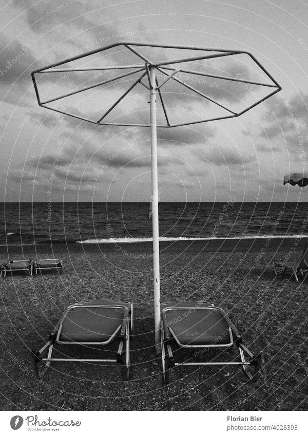 Zwei zusammengeklappte Sonnenliegen unter einem eisernen Sonnenschirmgestell ohne Stoff an einem Kiesstrand am Meer Strandliege Liege Erholung Küste Liegestuhl