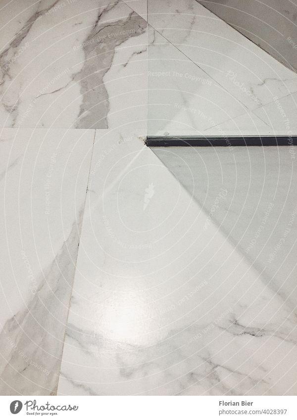 Geometrisch verlegter Marmorfußboden im Badezimmer mit einer Glaswand für die Dusche Bodenbelag Marmorboden marmoriert Marmorierung Stein Muster grafisch