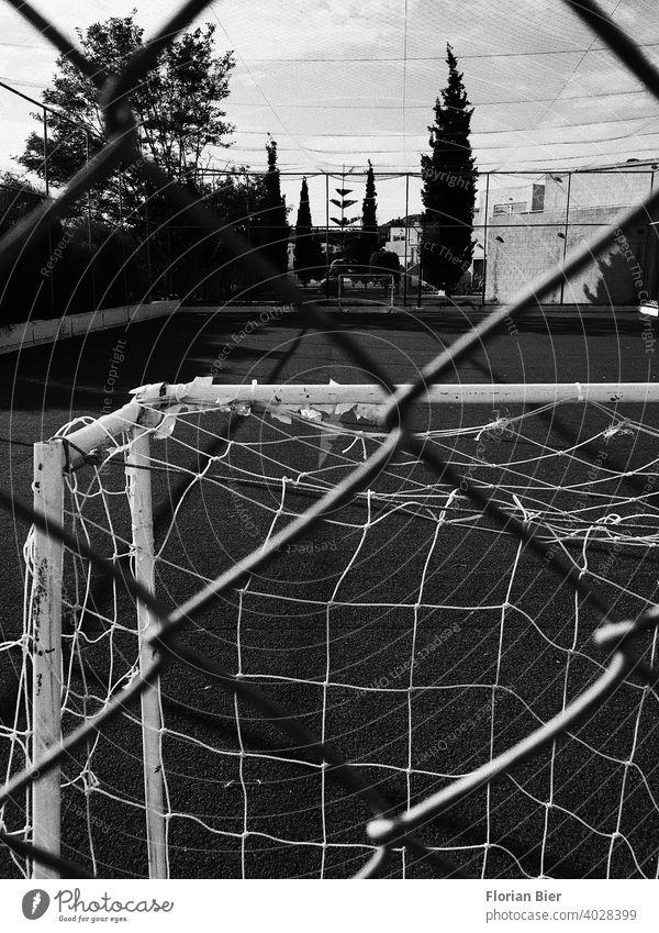 Blick durch einen Zaun auf einen Sportplatz im freien mit gegenüberstehenden Fußballtoren Zuschauer Einblick Hartplatz Belag Spielfeldbegrenzung Trainingsplatz