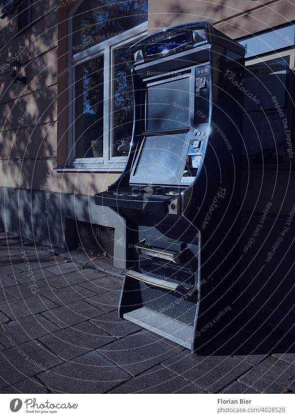 Abgestellter Spielautomat im öffentlichen Raum vor einer Wohnhausfassade arcade Zocken Spielen Schulden Sucht Suchtverhalten Spielsucht Geld Geldmünzen
