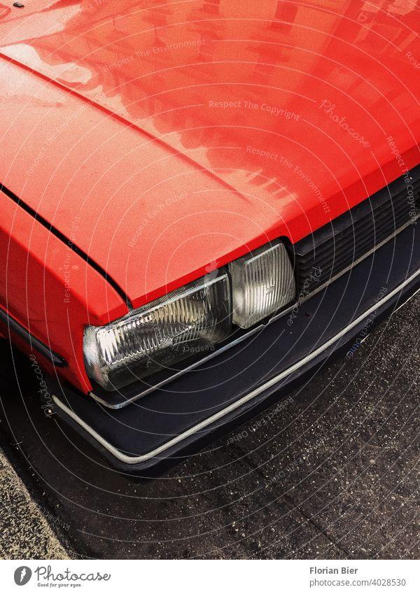Rot lackierte Motorhaube und eckiger Scheinwerfer sowie Kühlergrill und Kunstoffstoßstange eines geparkten Autos auf der Straße rot transparent Stoßstange