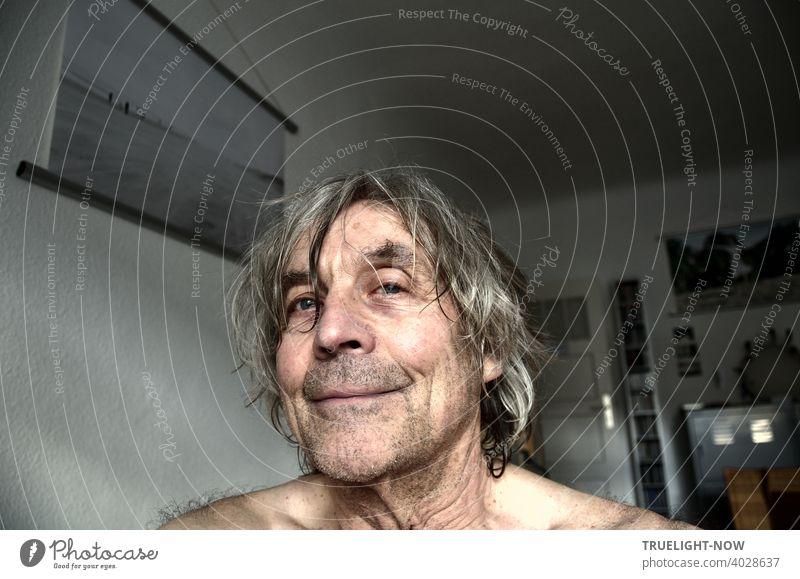Frontal Portrait eines Seniors in seinem Home Office, der sich zu freuen scheint, dass er den Haarschneider wegen der Pandemie seit über einem Jahr nicht aufsuchen konnte. An der Wand ein Foto des Photocase Users CL