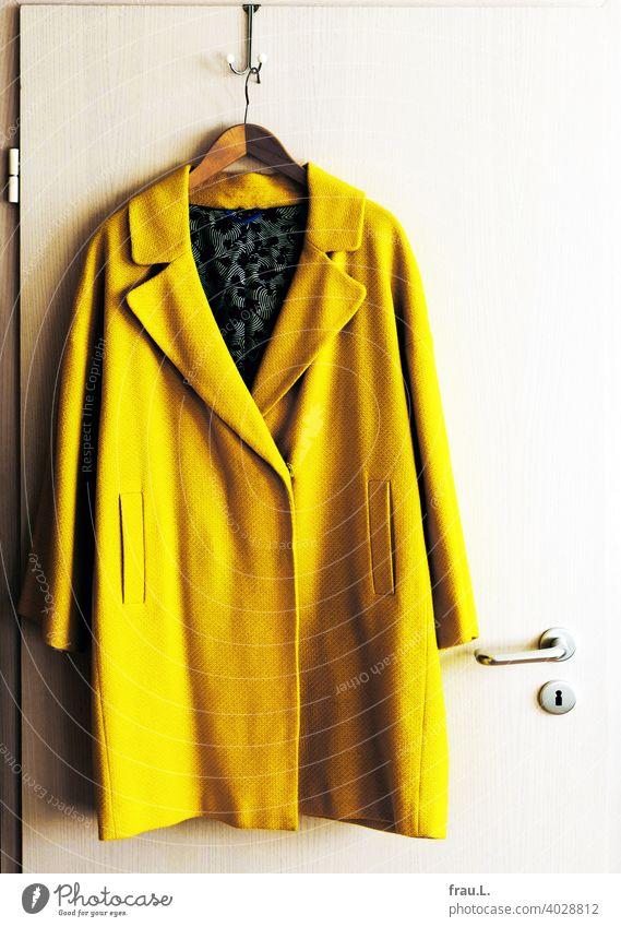 Ein Mantel hängt am Haken Innenaufnahme Übergangsmantel Tür Türklincke Kleiderbügel gelb Mode auffällig neongelb Sommermantel