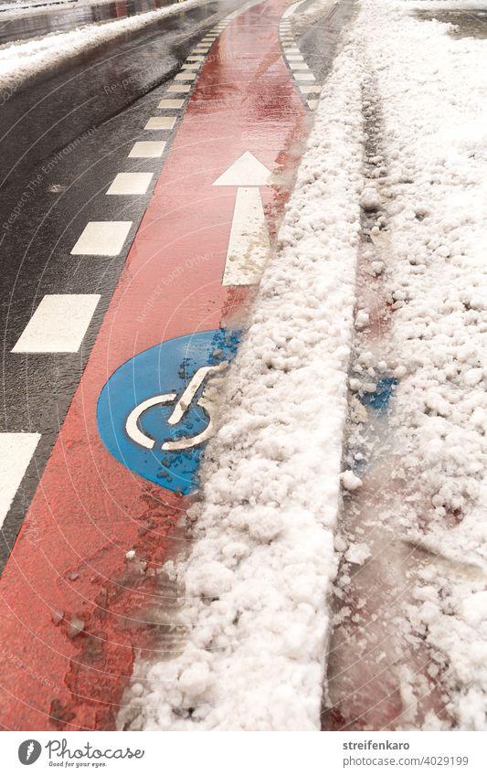 Freie Fahrt voraus! - Roter Fahrradweg drängt sich unter dem Schnee hervor Fahrrad fahren Rad fahren Winter Straße rot blau Symbol Verkehr Verkehrsmittel