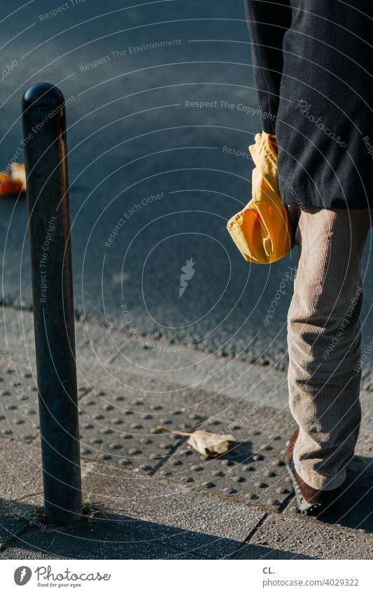 am straßenrand Mann Straße Poller Person Beutel Tasche gelb Bein Hose Jacke gehweg cordhose stehen Außenaufnahme Farbfoto Mensch anonym Anschnitt 1 Tag