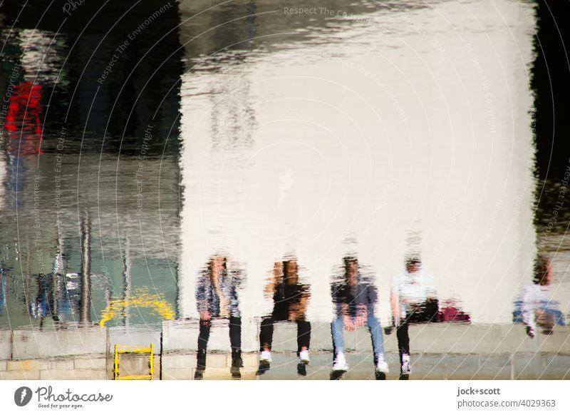 Vier Personen sitzen in der Sonne am ruhigen Fluss Moderne Architektur Spree Wasseroberfläche Reflexion & Spiegelung verschwommen Spreebogen Sonnenschein