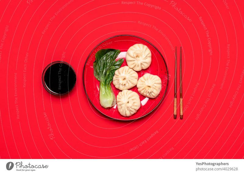 Baozi-Knödel mit Bok Choy auf einem roten Teller, Ansicht von oben. Hausgemachte chinesische gedämpfte Speisen obere Ansicht asiatisch Bao-Knödel Bapao Bok Choi