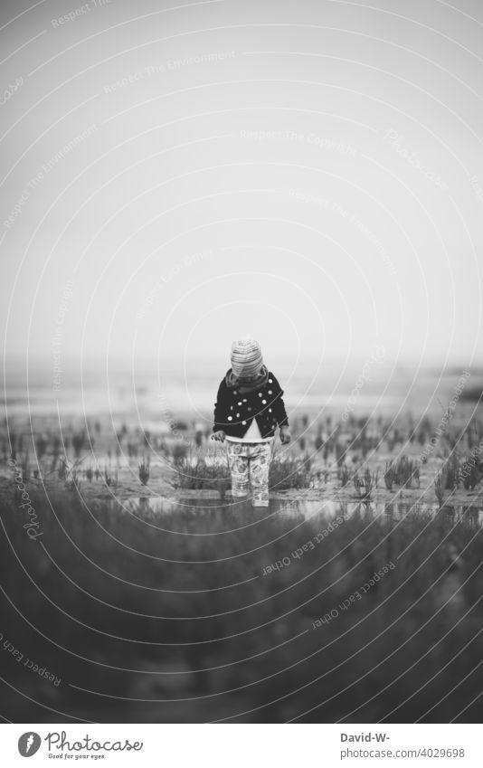 kleines Kind steht im Watt betrachtet die Natur Wattenmeer erkunden Meer alleine beobachten interessiert Nordseeküste Ferien & Urlaub & Reisen neugierig Mädchen