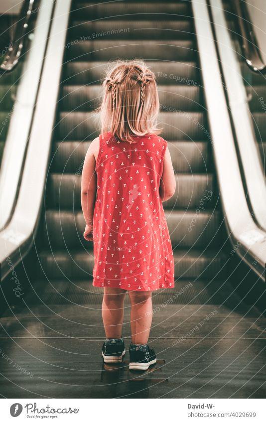 Mädchen in Gedanken steht vor einer Rollstreppe Kleid Rolltreppe einkaufen Einkaufszentrum alleine Kind gefahr verloren ängstlich Kaufhaus Angst