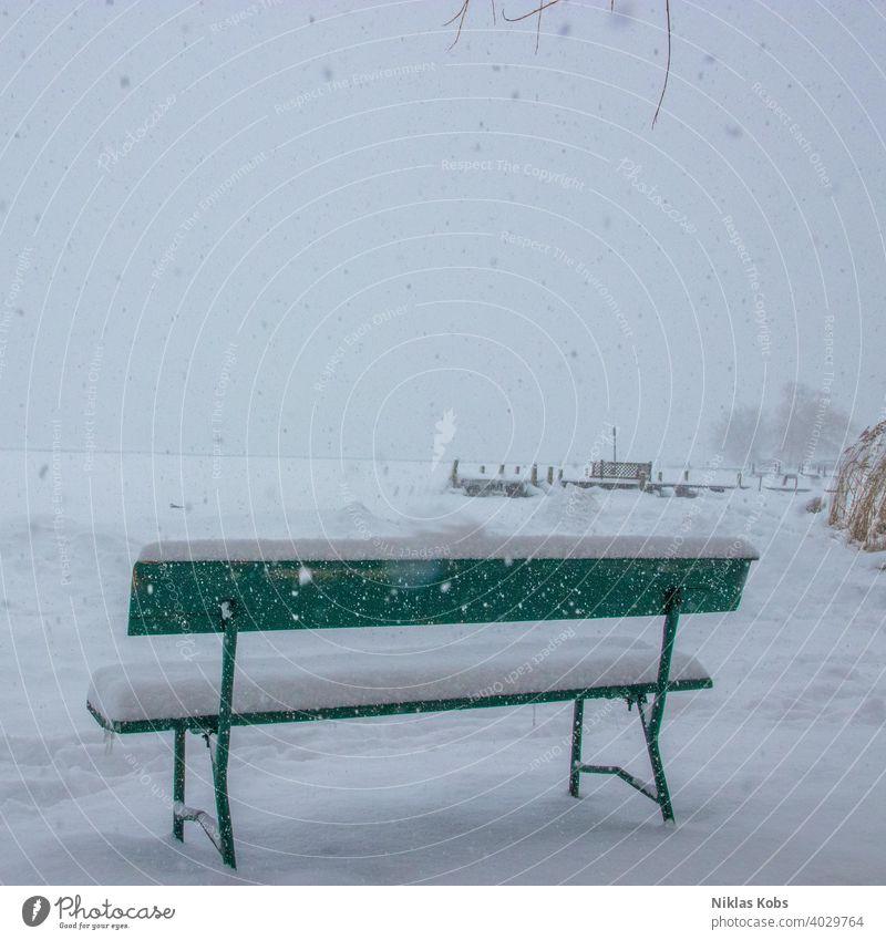 Bank im Schneetreiben kalt Winter Eis weiß Natur Frost Schneefall Schneeflocke Umwelt Winterstimmung grau Menschenleer Farbfoto Schneelandschaft Klimawandel