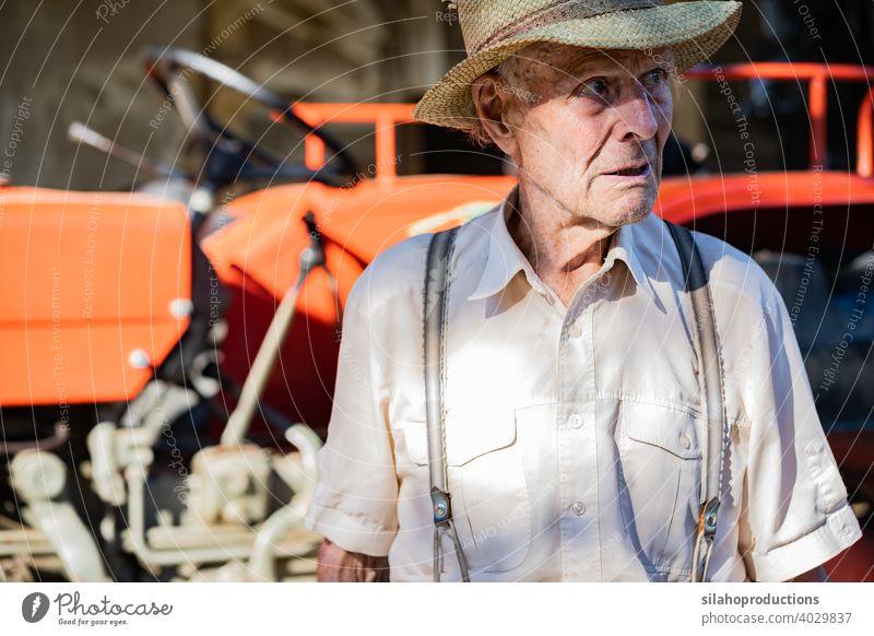 Porträt eines sehr alten Bauern mit Strohhut, der vor einem roten Traktor das Leben erklärt. Generation Erwachsener gealtert Ackerbau Auto Automobil PKW