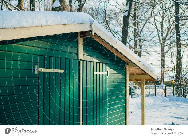 grüne Holzhütte im Winter bei Schnee im Wald Bauwerk Dach Haus Holzfassade Tor Tür Waldrand grünes Holz Außenaufnahme Farbfoto Menschenleer Hütte Gebäude