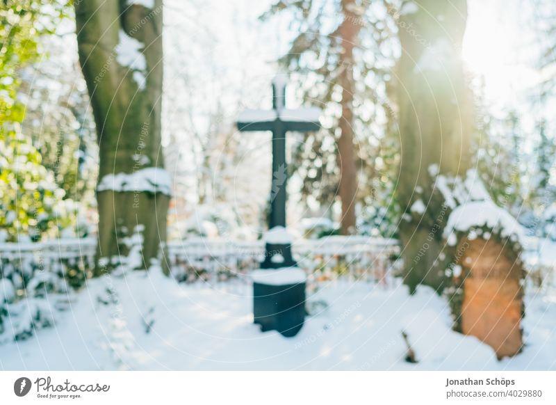 Grab auf Friedhof im Winter bei Schnee Tod und Ewigkeit Abschied Beerdigung Bokeh Christentum Coronatote Coronawinter Gebet Gedenken Gegenlicht Glaube Gott