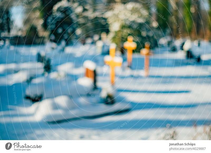 Grab auf Friedhof im Winter bei Schnee Tod und Ewigkeit Abschied Beerdigung Bokeh Christentum Coronatote Coronawinter Gebet Gedenken Glaube Gott Gottesacker