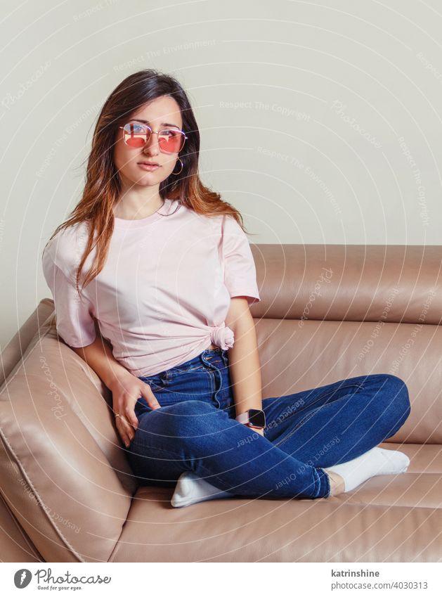 Junge Frauen sitzen auf dem Sofa zu Hause jung anhaben Attrappe T-Shirt Sonnenbrille Lifestyle Jeanshose Brille im Innenbereich sich[Akk] entspannen lange Haare