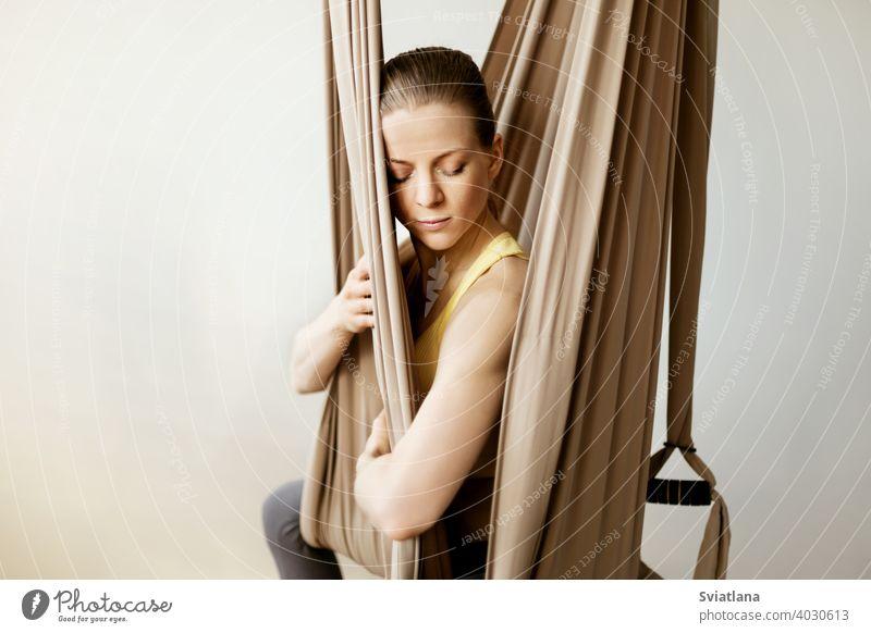 Eine junge Frau meditiert, während sie in einer Hängematte in einer Yogastunde sitzt. Aero Yoga, Sport, gesunder Lebensstil Fitness sich[Akk] entspannen Mädchen