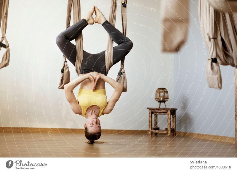 Sport Mädchen ist in Aero Yoga beschäftigt und führt Asanas mit Hilfe der Hängematte. Yoga, Fitness, Sport Übung Antigravitation Frau Pose Fitnessstudio passen