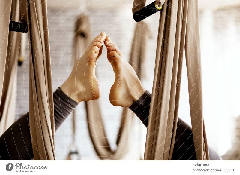 Nahaufnahme einer Frau die Beine in einer Hängematte tun aerial Yoga-Übungen in der Turnhalle Antenne Fitnessstudio schließen Lifestyle Gleichgewicht passen
