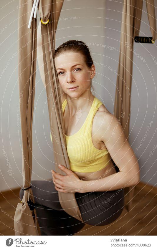 Ein junges Mädchen entspannt sich nach einem Yoga-Workout und sitzt in einer Hängematte für Anti-Schwerkraft-Luft-Yoga. Harmonie, Achtsamkeit und ein gesunder Lebensstil