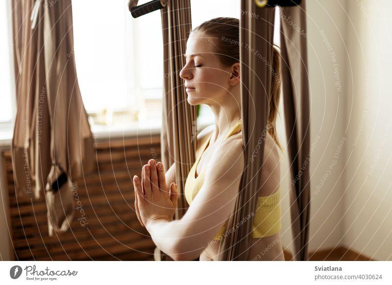 Eine junge Frau meditiert in einer Hängematte nach einer Aero-Yoga-Stunde. Yoga-Meditation in einer Hängematte. Gesunder Lebensstil und Entspannungskonzept