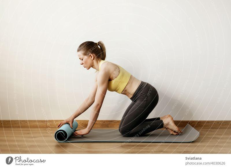 Ein junges Mädchen rollt eine Yogamatte aus, bevor sie eine Yogastunde nimmt. Yoga, Fitness, Lebensstil Pose Stehen Frau Körper Übung Atelier erweitert Seite