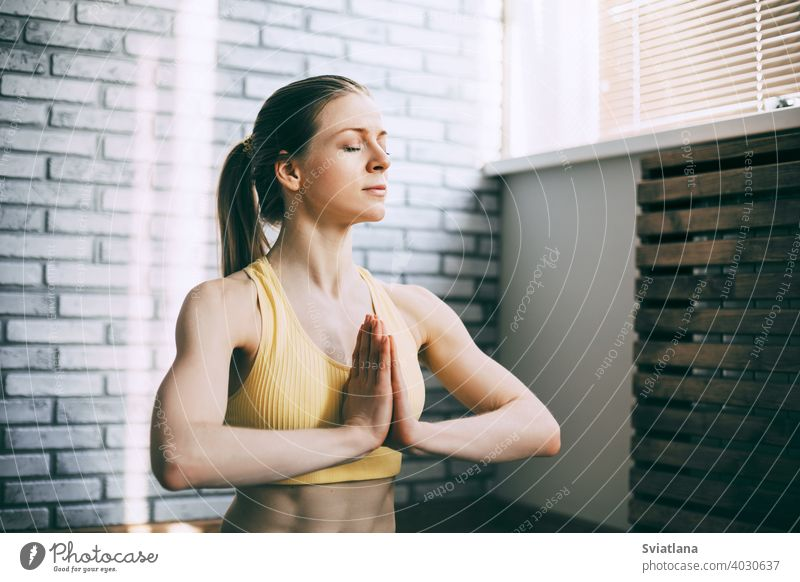 Ein blondes Mädchen ruht sich nach einem Fitnesskurs aus und meditiert. Das Konzept von Sport und einem gesunden Lebensstil. Yoga, Meditation meditierend jung