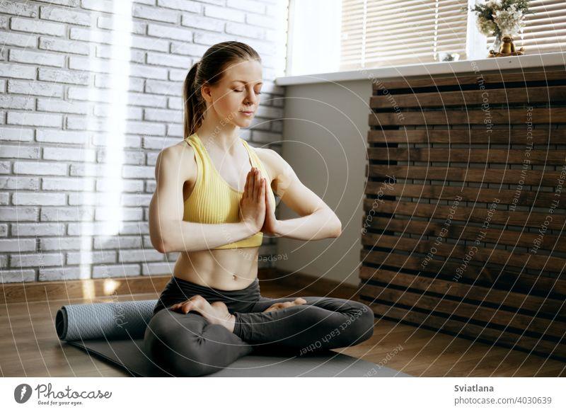 Ein schönes Mädchen sitzt im Lotussitz und meditiert. Yoga, Fitness, Meditation. Gesunder Lebensstil Konzept meditierend jung positionieren Lotos Frau Lifestyle