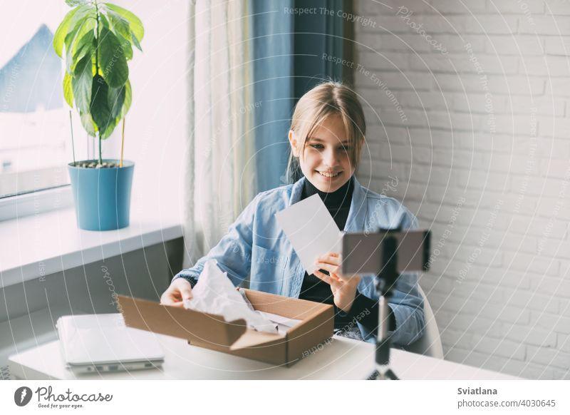 Ein Teenager-Blogger nimmt ein Video auf und packt ein Paket für seinen Blog mit einem Smartphone auf einem Stativ zu Hause aus. Kommunikation eines Video-Blogger-Mädchens in sozialen Netzwerken mit Abonnenten und Freunden.