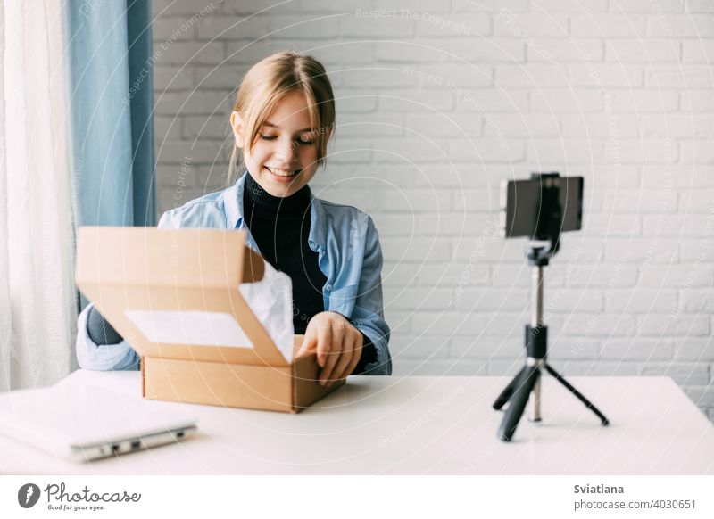 Ein jugendlicher Blogger nimmt mit einem Smartphone auf einem Stativ zu Hause ein Video auf und packt einen Karton für seinen Blog aus. Kommunikation eines Video-Blogger-Mädchens in sozialen Netzwerken mit Abonnenten und Freunden