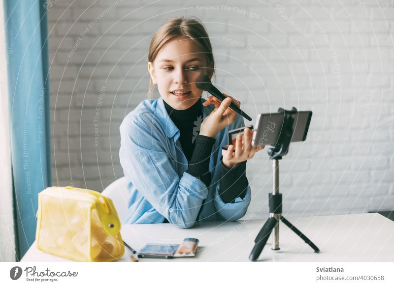 Ein Teenager-Mädchen schminkt sich und nimmt mit einem Smartphone auf einem Stativ zu Hause ein Video für ihren Blog auf. Kommunikation eines Video-Blogger-Mädchens in sozialen Netzwerken mit Abonnenten und Freunden