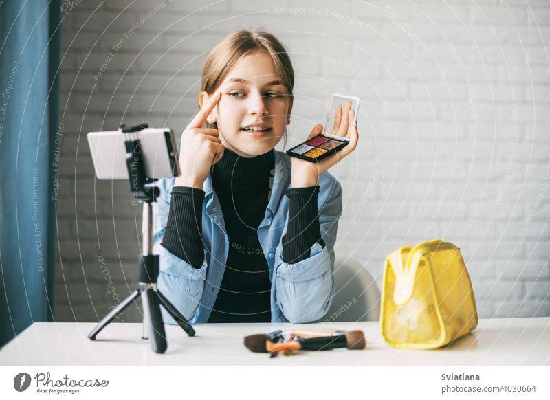 Ein Teenager-Mädchen schminkt sich und zeigt, wie man Rouge aufträgt, während sie mit ihrem Smartphone auf einem Stativ zu Hause ein Video für ihren Blog aufnimmt