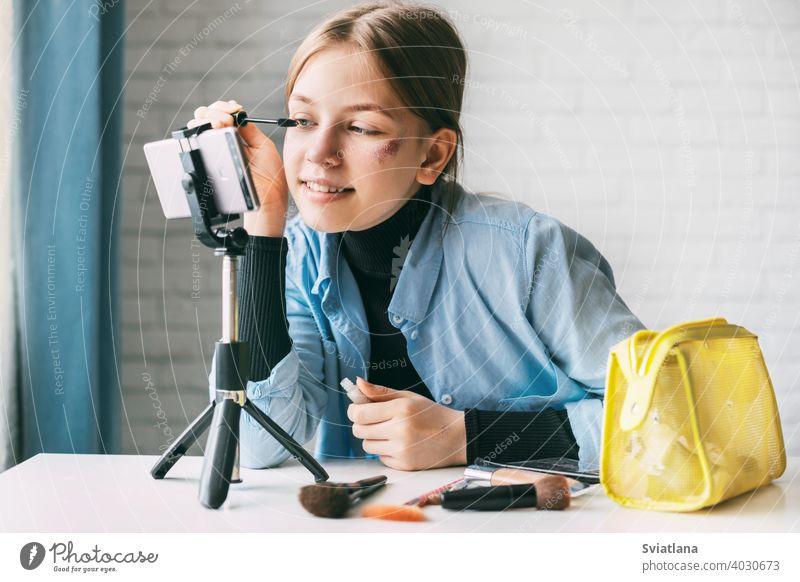 Ein Teenager-Mädchen zeigt, wie sie ihre Augenbrauen und Wimpern färbt, während sie ein Video für ihren Blog mit einem Smartphone auf einem Stativ zu Hause aufnimmt. friends