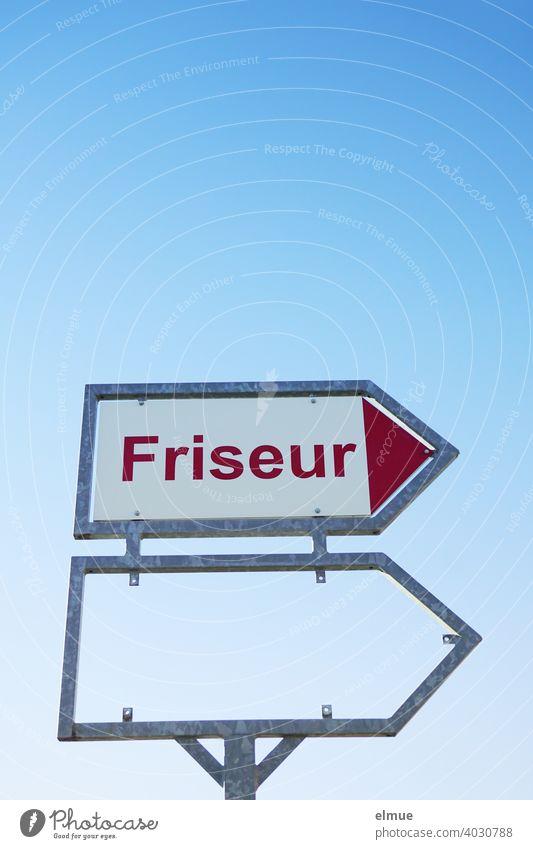 """Hinweisschild mit roter Druckschrift """"Friseur"""" sowie ein leerer Rahmen für ein weiteres Schild vor blauem Himmel / Friseurtermin Frisör Hairstylist"""