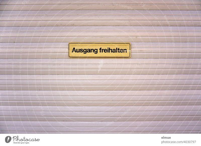 """""""Ausgang freihalten"""" steht auf einem Schild an einem Garagentor / Rücksichtnahme Tor Mitteilung Hinweisschild Schilder & Markierungen Ausfahrt Einfahrt Eingang"""
