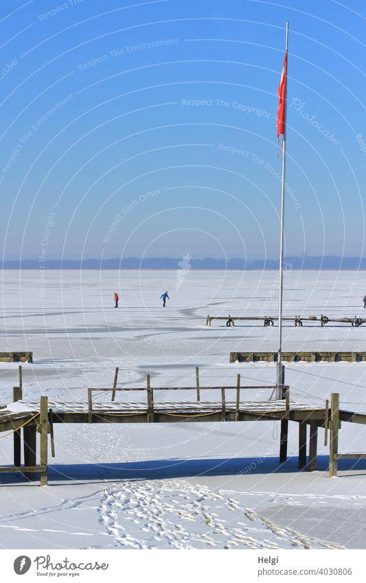 zugefrorener See mit Schnee, Spuren, Holzstegen, einer Fahnenstange und im Hintergrund zwei Menschen, die Schlittschuh laufen Winter Frost Eis Kälte Steg