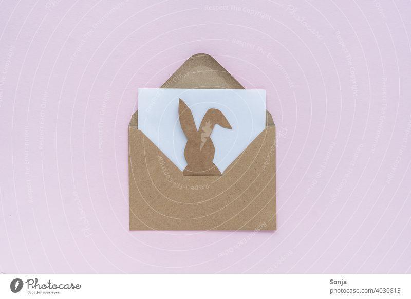 Braunes Briefkuvert mit einem Papierosterhasen auf einem rosa Hintergrund briefkuvert offen Osterhase Ostern Botschaft Nachricht Hase & Kaninchen lustig Freude