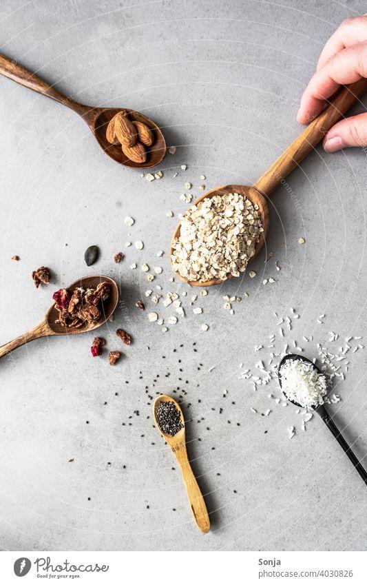 Müsli Zutaten auf Löffeln auf einem rustikalen Hintergrund Hand Frühstück Ernährung Diät organisch Haferflocken Mandel chiasamen Kokosflocken Morgen