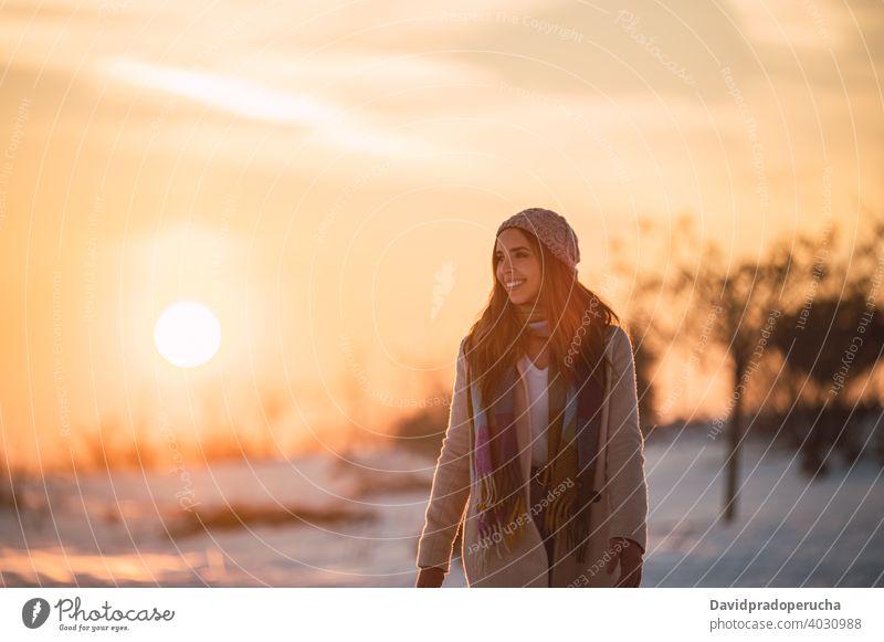 Frau zu Fuß auf verschneiten Feld bei Sonnenuntergang Winter Landschaft Schnee Glück Spaziergang Natur Saison genießen froh frisch kalt heiter schlendern