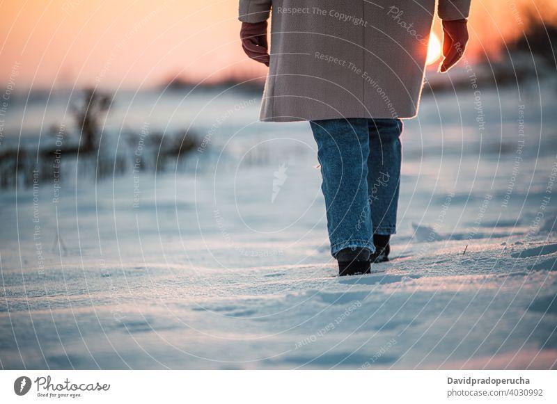 Anonyme Person geht auf verschneitem Feld Winter Schnee Spaziergang Bein Stiefel Fußspur Sonnenuntergang allein Natur Saison Sohle frisch Landschaft kalt Wetter