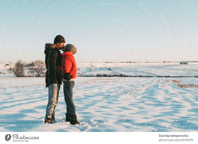 Paar küssen in verschneiten Feld Kuss Winter Schnee Landschaft Liebe romantisch Zusammensein Partnerschaft Umarmung Zuneigung Umarmen amourös Angebot Bonden