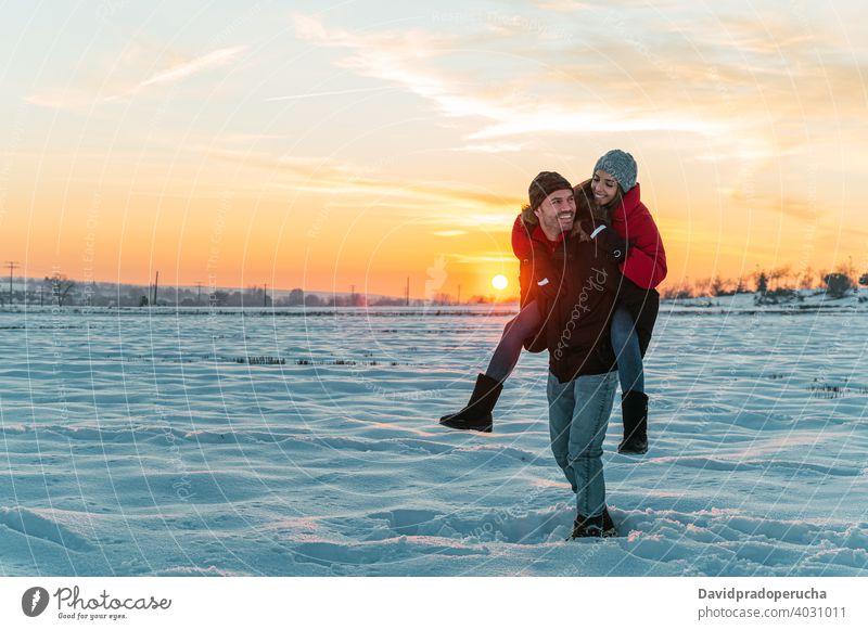 Glückliches Paar mit Spaß in verschneiten Feld Huckepack Winter Schnee Spaß haben heiter Landschaft Liebe Zusammensein Mitfahrgelegenheit Freude Lachen