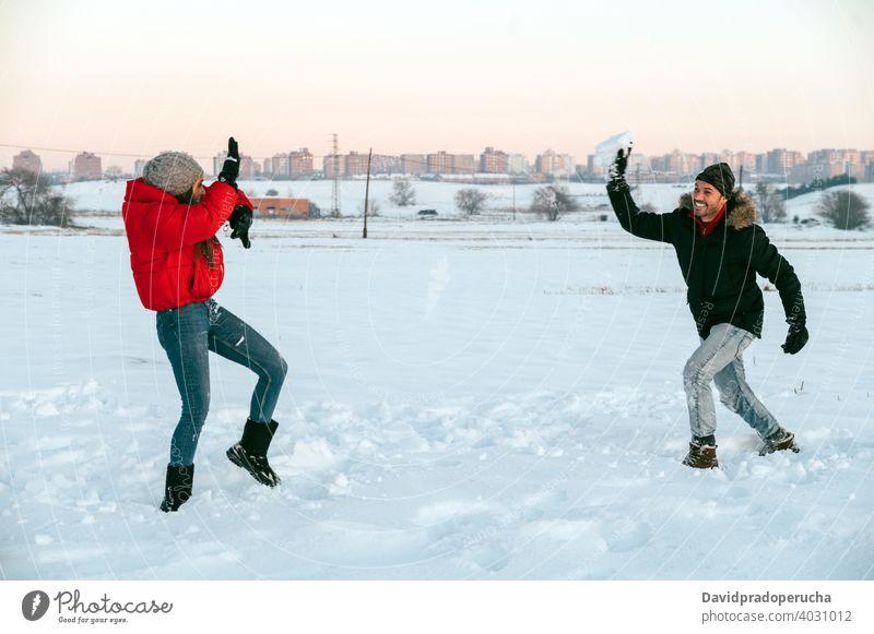 Fröhliches Paar spielt Schneebälle im Winter Feld Schneeball Spaß haben spielen heiter genießen Zusammensein Landschaft Liebe romantisch Partnerschaft Zuneigung