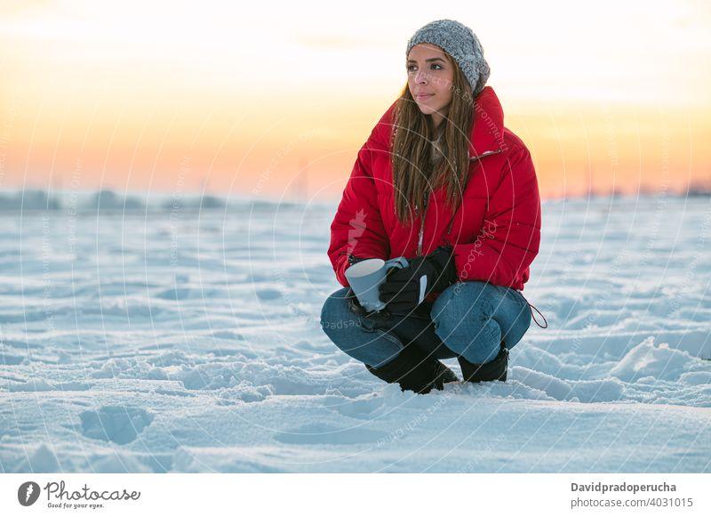 Frau mit Tasse Kaffee ruht in verschneiten Feld Winter Wanderer Schnee trinken ruhen Sonnenuntergang Natur kalt Windstille nachdenken Becher Heißgetränk Abend