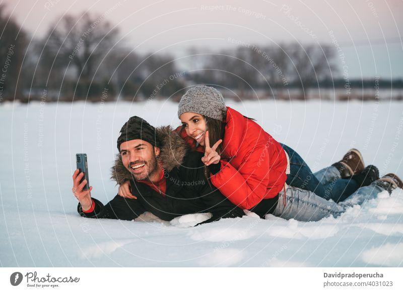 Lachendes Paar nimmt Selfie auf Schnee Winter Spaß haben heiter Landschaft Liebe Zusammensein Smartphone Freude Feld romantisch Partnerschaft Zuneigung