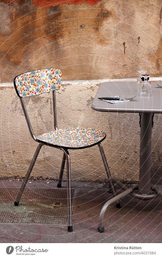 hübsch gemusterter stuhl im straßencafé tisch draußen wand fassade küchenstuhl retro vintage bistro restaurant gastronomie urban gläser besteck resopal