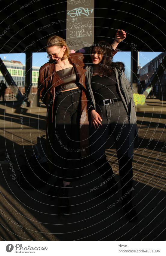 Lara und Estila frau langhaarig stehen cool freundschaft mantel lässig blond dunkelhaarig architektur brücke sonnig sonnenlicht miteinander beieinander zusammen